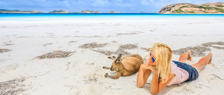 A woman relaxing on an Australian beach with a kangaroo