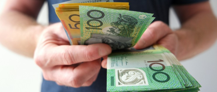 A man holding a large amount of Australian dollar notes.