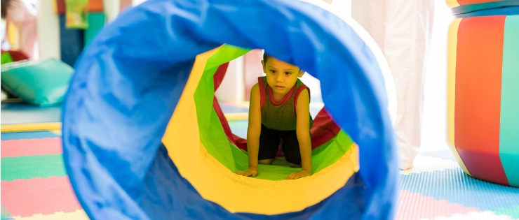 Child crawling through a bright coloured tunnel taking part in occupational therapy.