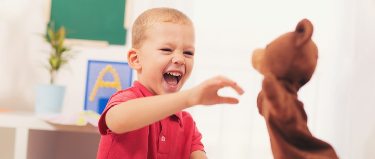 Young boy playing with a bear hand puppet to help treat autism (Asperger's syndrome).