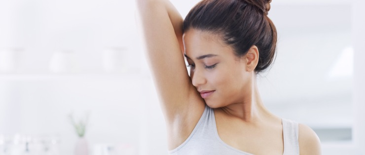Young female smelling underarm to determine if her deodorant is stopped sweat production
