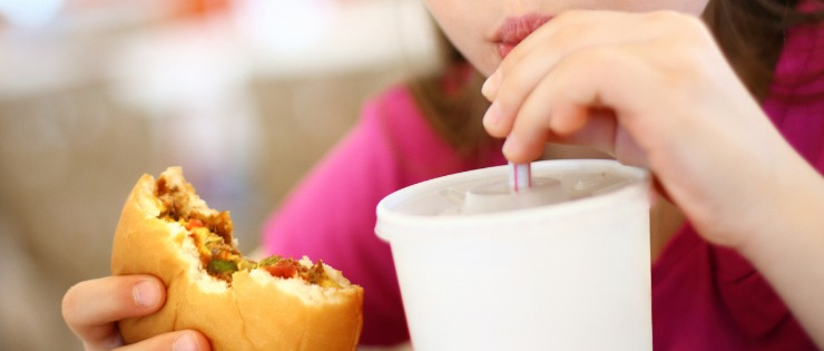 A young girl consuming fast food and a milkshake