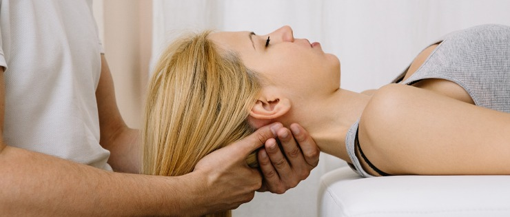 Chiropractor assessing a female patients neck pain.