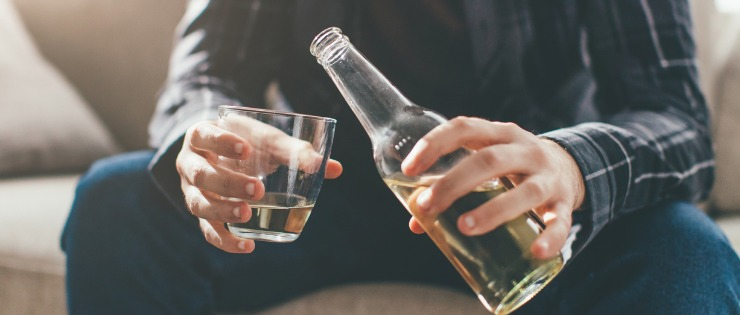 Man pouring an alcoholic drink, too much alcohol consumption can lead to chronic disease