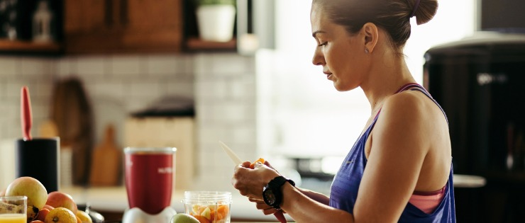Female making a healthy breakfast smoothie with fruit and vegetables in workout clothing