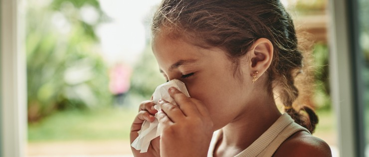 Young girl blowing her nose due to an allergic reaction.