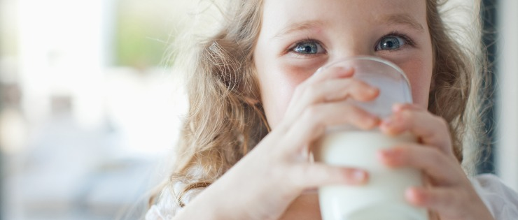 Young girl drinking a glass of dairy milk.