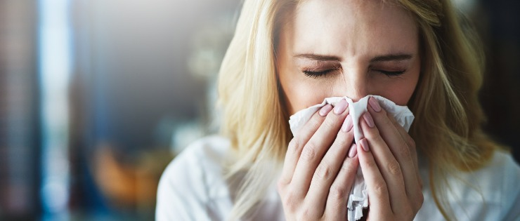 Women suffering from a cold blowing her nose