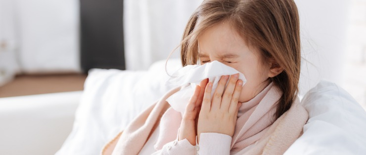 Young girl sick with the common cold blowing her nose