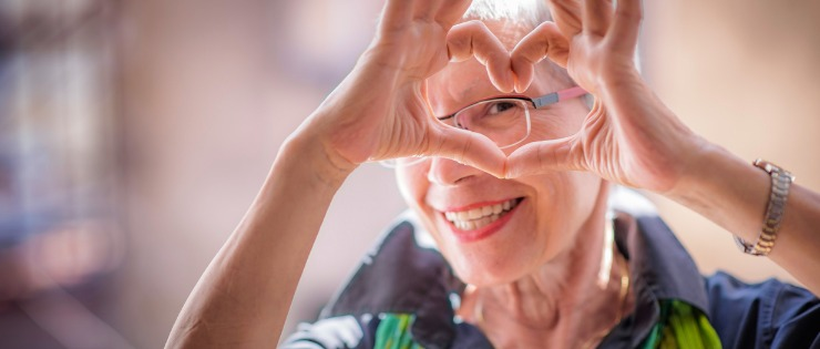 Elderly lady making a love heart with her hands as she is taking care of her mental health.