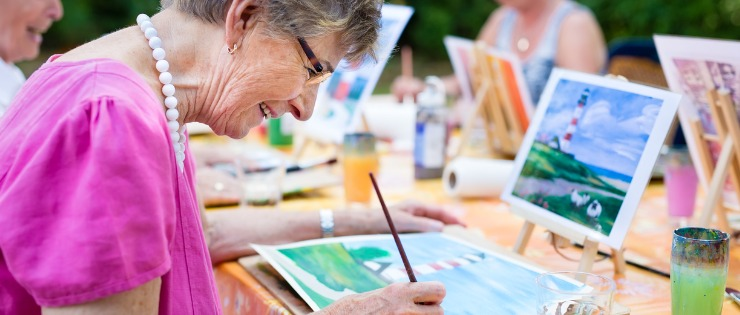 Senior woman painting a picture at a social club, so she can stay mentally active.