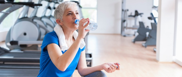Mature aged woman drinking lots of water after a gym workout
