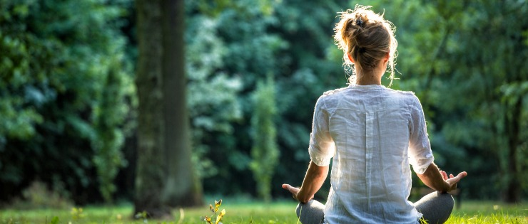 A woman in a park making time for herself and meditating