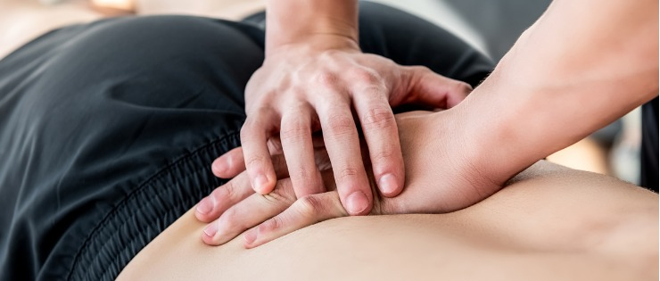 Osteopath using hands-on treatment to support the movement of the lower back