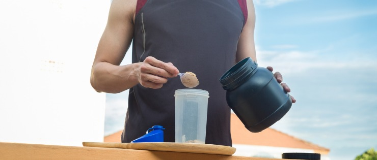 A man making a protein shake after a workout.