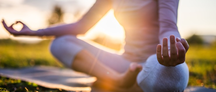 Young woman meditating in a park at sunset