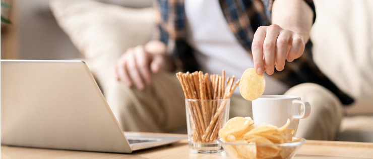 Young man working from home reach for a bowl of snacks to eat while being bored