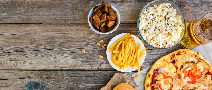 Flat lay of salty foods that should be avoided before training such as hot chips, popcorn and pizza