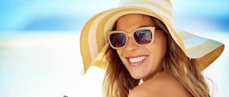 woman in a hat on the beach wearing sunglasses to protect her eyes