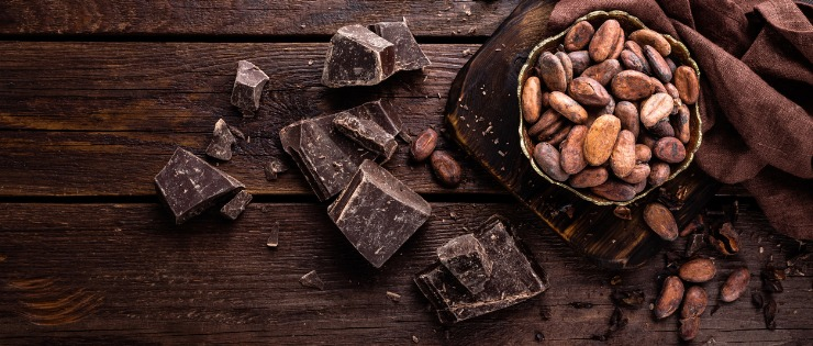 Dark chocolate pieces and cocoa beans on a brown wooden background