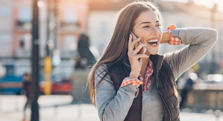 A smiling woman talking on the phone while away on holiday