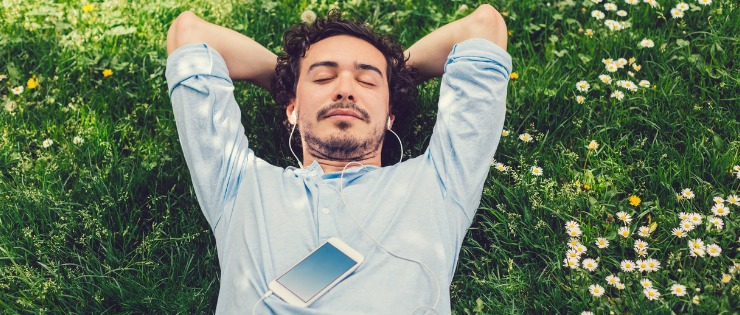 A man having laying on the grass, resting and reducing elevated cortisol levels