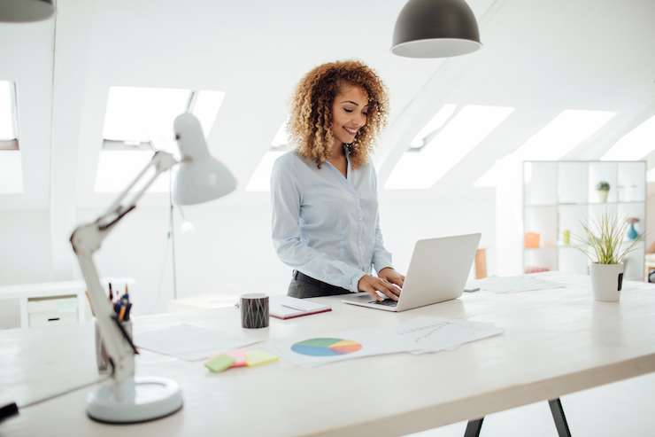 women standing at sit stand desk to keep healthy